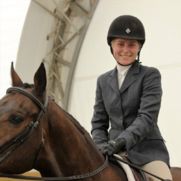 young equestrian rider sitting atop her horse and smiling
