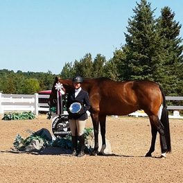 young equestrian rider standing next to her horse at a horse show with her prizes in hand